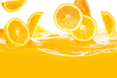 Fresh oranges falling in juice Stock Photo