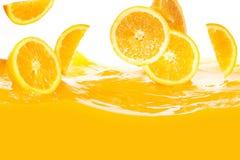 Fresh oranges falling in juice Stock Photo