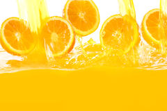 Fresh oranges falling in juice royalty free stock photos