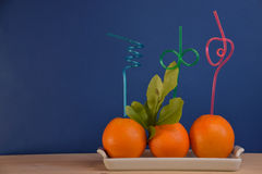Fresh oranges with fancy colorful straws Stock Photography