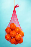 Fresh oranges fruits in mesh from supermarket. Mesh bag of fresh oranges healthy tropical fruits from supermarket on blue. Food retail Stock Photo