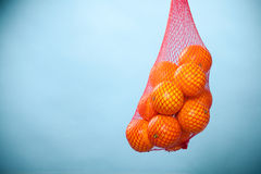 Fresh oranges fruits in mesh from supermarket. Mesh bag of fresh oranges healthy tropical fruits from supermarket on blue. Food retail Royalty Free Stock Images