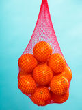 Fresh oranges fruits in mesh from supermarket. Mesh bag of fresh oranges healthy tropical fruits from supermarket on blue. Food retail Stock Photos
