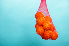 Fresh oranges fruits in mesh from supermarket. Mesh bag of fresh oranges healthy tropical fruits from supermarket on blue. Food retail Royalty Free Stock Photography