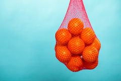 Fresh oranges fruits in mesh from supermarket. Mesh bag of fresh oranges healthy tropical fruits from supermarket on blue. Food retail Royalty Free Stock Photo