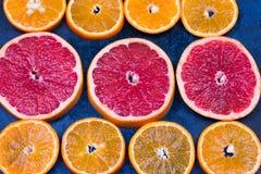 Fresh oranges, grapefruits and madarine slices on dark stone background. Stock Photos