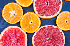 Fresh oranges, grapefruits and madarine slices on dark stone background. Stock Images