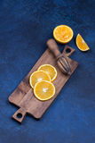 Fresh oranges, grapefruits and madarine slices on dark stone background. Fresh oranges, grapefruits and madarine slices on dark blue stone background. Rustic royalty free stock images