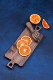 Fresh oranges, grapefruits and madarine slices on dark stone background. Stock Image