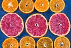 Fresh oranges, grapefruits and madarine slices on dark stone background. Stock Photo