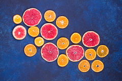 Fresh oranges, grapefruits and madarine slices on dark stone background. Royalty Free Stock Images