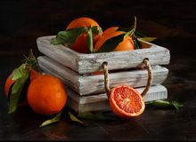 Fresh  oranges with leaves. On an old table Royalty Free Stock Photos