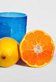 Fresh oranges and lemon with blue glass Royalty Free Stock Photos