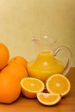 Fresh oranges and orange juice. Oranges and a jug of orange juice Royalty Free Stock Photography