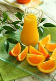 Fresh oranges and orange juice in glass Stock Image