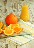 Fresh oranges and orange juice in glass Stock Images