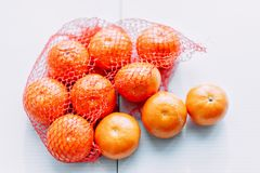 Oranges in net on white backgroung not isolated. Fresh oranges in plastic mesh sack on white table Stock Photography