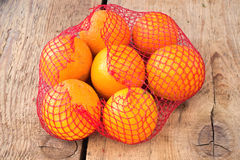Fresh oranges in plastic net Stock Photo