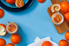 Sweet jam from oranges in small jars with fresh oranges. Fresh oranges on the plate, orange jam on the blue table. Copy text space Stock Photography
