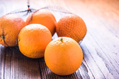 Fresh oranges in shopping net or bag. On wooden rustic table, copy text space Stock Photography