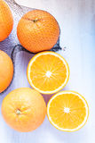 Fresh oranges in shopping net or bag. On wooden rustic table, copy text space Stock Images