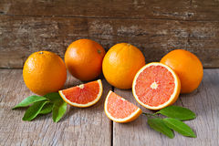 Fresh oranges with slices and leaves on wooden background. Stock Photography