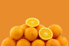 Fresh oranges and two halves. On a orange background stock photography