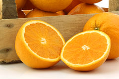 Fresh oranges and two halves in a wooden box Royalty Free Stock Image