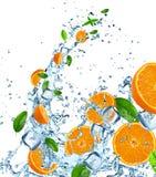 Fresh oranges in water splash over white Stock Image