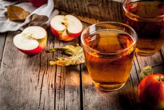 Fresh organic apple juice. Fresh organic farm apple juice in glasses with raw whole and sliced red apples, on old rustic wooden table, copy space royalty free stock photo