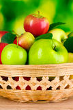 Fresh organic apples in basket on wooden table Stock Photo