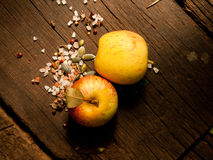 Fresh organic apples on a textured wooden table with sunlight. Warm light and wooden textures. Royalty Free Stock Photos