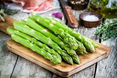 Fresh organic asparagus on a cutting board with Parma ham Royalty Free Stock Photos