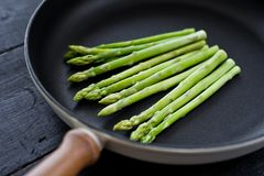 Fresh organic asparagus in a frying pan. Black background, top view, space for text. stock photography