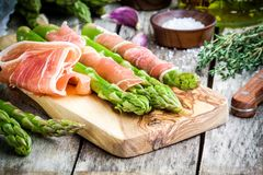 Fresh organic asparagus with prosciutto on a cutting board Royalty Free Stock Image