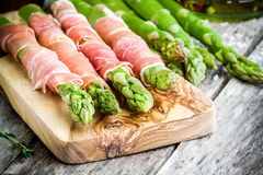 Fresh organic asparagus wrapped in Parma ham on a cutting board Royalty Free Stock Photography