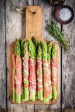 Fresh organic asparagus wrapped in Parma ham on a cutting board Stock Photography