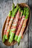 Fresh organic asparagus wrapped in Parma ham on a cutting board Royalty Free Stock Photos