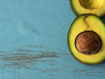 Fresh organic avocado on blue old wooden table, top view with copy space Royalty Free Stock Photos
