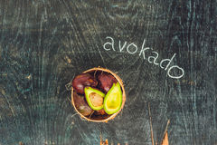 Fresh organic avocado on dark old wooden table, side view Royalty Free Stock Photos