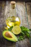 Fresh organic avocado, lime, parsley and olive oil on  old wood Stock Photos