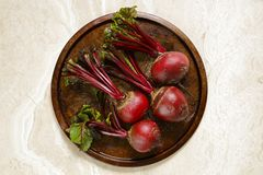 Fresh beetroots on metal tray. Fresh organic beetroots on round metal tray on marble table Stock Images