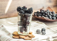 Fresh organic blackberries in a glass on a gray wooden table, ru. Stic,selective focus Stock Photography