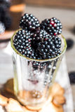 Fresh organic blackberries in a glass on a gray wooden table, ru. Stic,selective focus Royalty Free Stock Photos