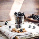 Fresh organic blackberries in a glass on a gray wooden table, ru. Stic,selective focus Royalty Free Stock Photo