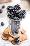 Fresh organic blackberries in a glass on a gray wooden table, ru. Stic,selective focus Royalty Free Stock Image