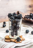 Fresh organic blackberries in a glass on a gray wooden table, ru. Stic,selective focus Stock Image