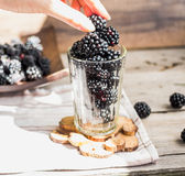 Fresh organic blackberries in a glass on a gray wooden table. Rustic,selective focus,eat hands Stock Image