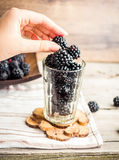 Fresh organic blackberries in a glass on a gray wooden table. Rustic,selective focus,eat hands Stock Photography