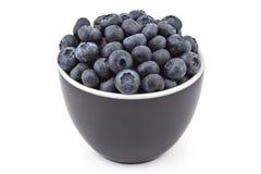 Fresh organic blueberries. Fresh ripe organic blueberries in a black bowl on a white background Royalty Free Stock Photo